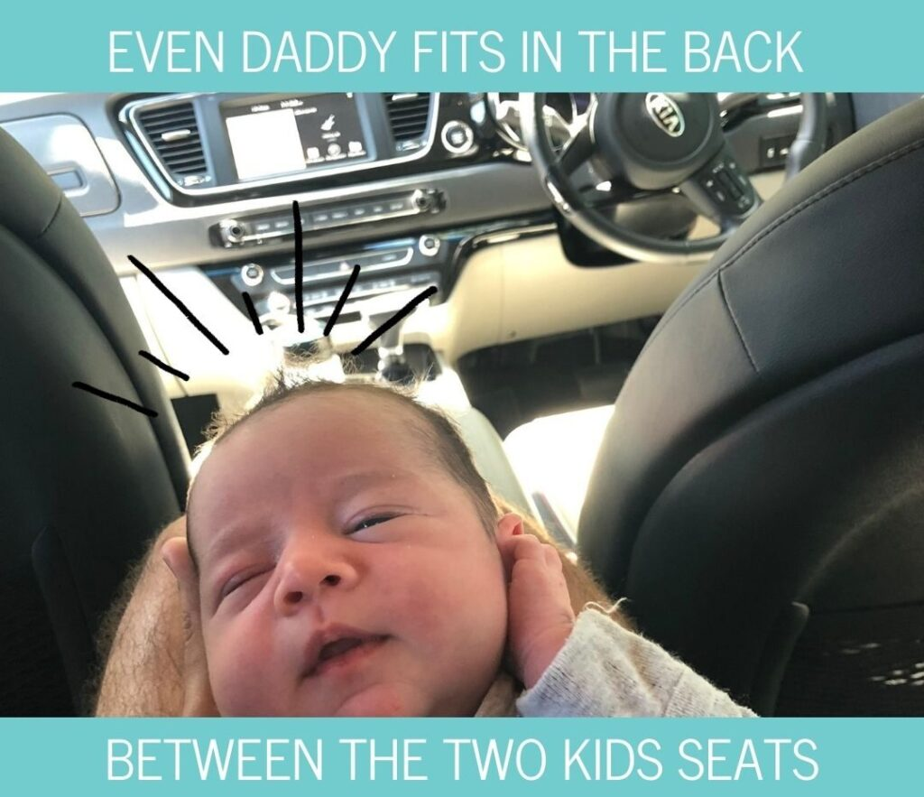 Even dad can fit between two child seats in the Kia Carnival